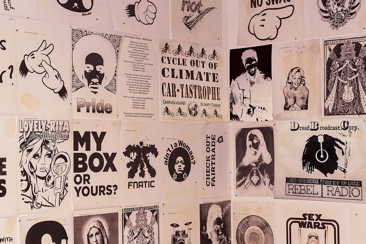 A wall-mounted montage of t-shirt printing designs at Fifth Column printers.