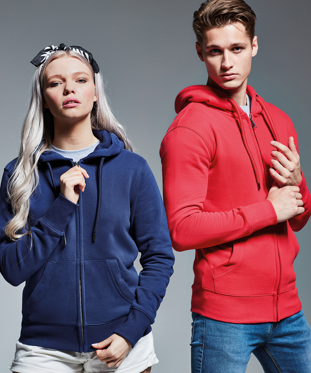 Studio photo with a man and woman wearing the Anthem zip hoodie (AM002).