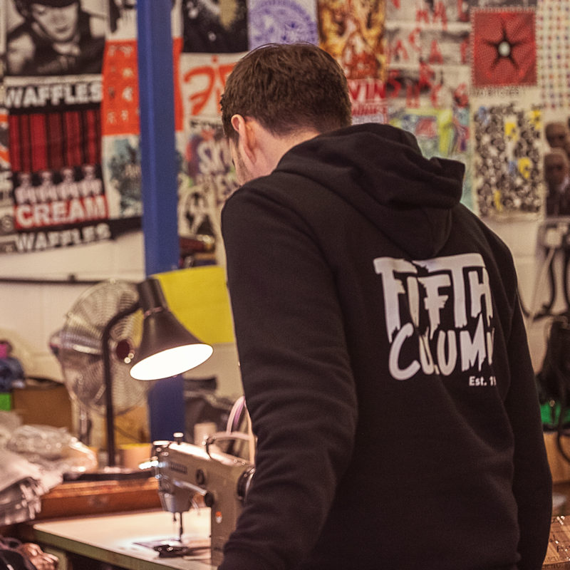 A man printing t-shirts and wearing a garment with Fifth Column printed on it.